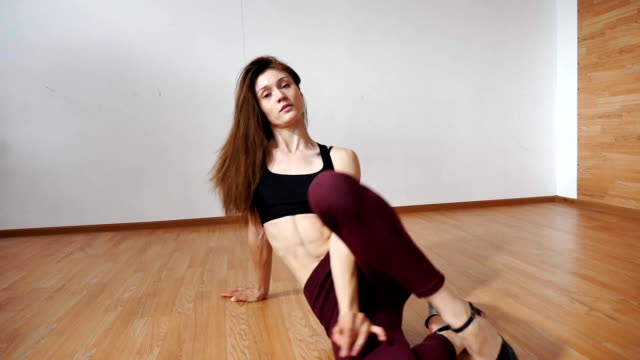 young woman ingirl in tights and top, high heels lying on the floor and dancing, video