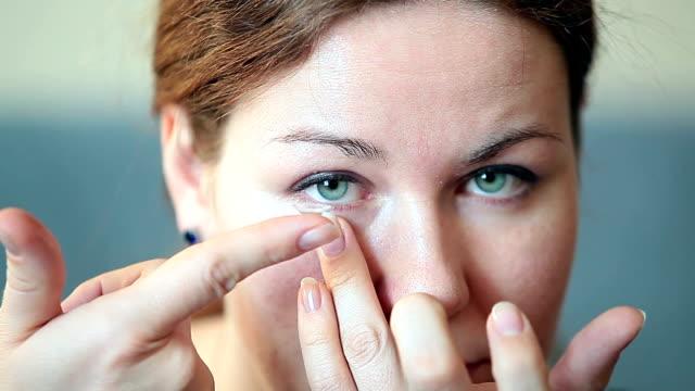 vídeos de stock e filmes b-roll de jovem mulher inserir claramente lente de contacto no seu olho - contacts