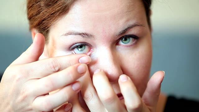 vídeos de stock e filmes b-roll de jovem mulher inserir límpida transparente lente de contacto - contacts