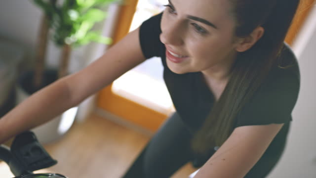 SLO MO Young woman intense cycling on the exercise bike Slow motion shot of a young woman intense cycling on the exercise bike at home. Conceptual shot of the self isolation time. Shoot in 8K resolution. exercise bike stock videos & royalty-free footage