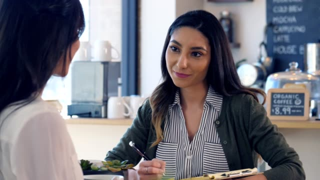 A young woman interviews another female for hire at a coffee shop.