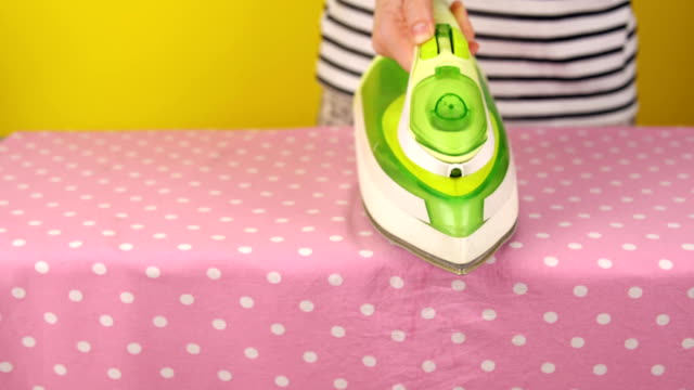 Young woman irons bed linen on an ironing board, household chores. video