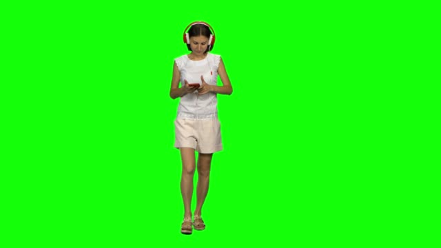 vídeos de stock e filmes b-roll de young woman is calmly walking in big red headphones, chooses music on the mobile phone on green screen. front view - teeshirt template