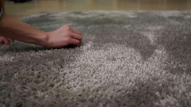 Young woman is cleaning the carpet in home video