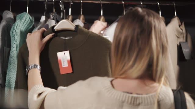 eine junge frau erwägt einen warmen pullover, auf dem ein tag mit einem preis wiegt - etikett stock-videos und b-roll-filmmaterial