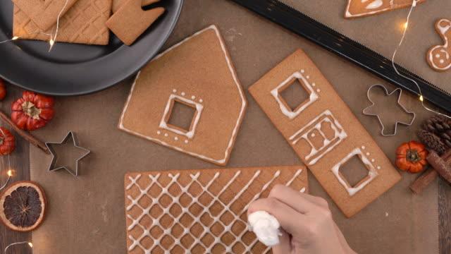 junge frau schmückt weihnachten lebkuchen haus kekse keks zu hause mit frosting topping in eisbeutel, nahaufnahme, lebensstil. - lebkuchenhaus stock-videos und b-roll-filmmaterial