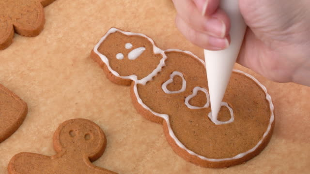 ung kvinna dekorerar jul pepparkakshus kakor kex hemma med glasyr topping i isning påse, när du vill, livsstil. - pepparkaka bildbanksvideor och videomaterial från bakom kulisserna