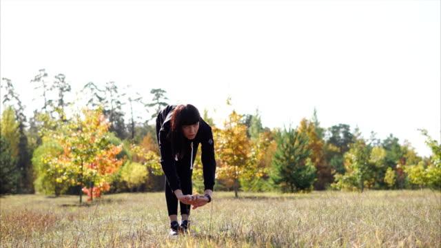 若い女性が草原のウォーム アップをやっています。 - チャームポイント点の映像素材/bロール