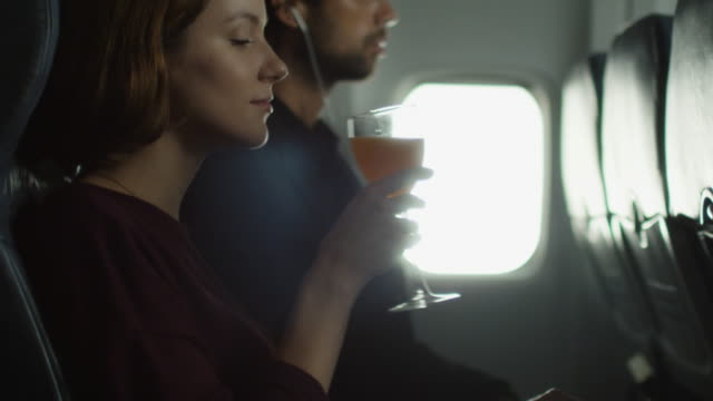 Young woman is drinking a cocktail on an airplane and a man is listening to music in the background next to a window. video