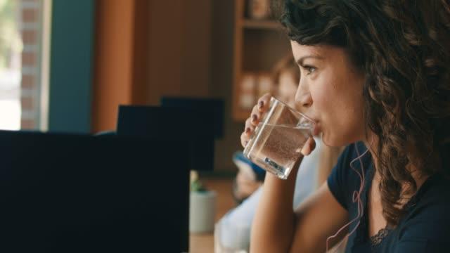 young woman is having a glass of water - napój filmów i materiałów b-roll