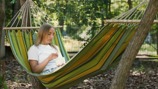 Young woman is having a rest, lying in colorful hammock and eating tasty ice cream. Summer sunny day in city park with green trees. Copy space