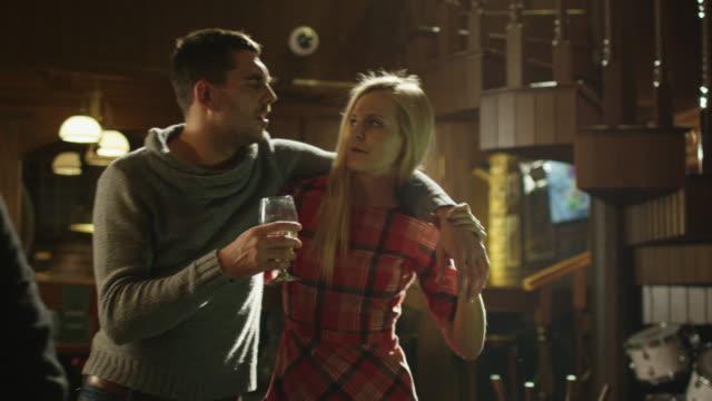 vídeos de stock e filmes b-roll de jovem mulher ajudando a sua bebida amigo com copo de cerveja para ir longe da barra. - bêbedo