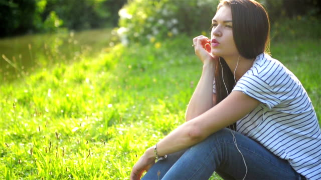 Young Woman is Listening Music Using Earphones Outdoors. Pretty Girl in Striped Shirt Enjoy the Song at Her Earbuds. Green Grass on the Background video
