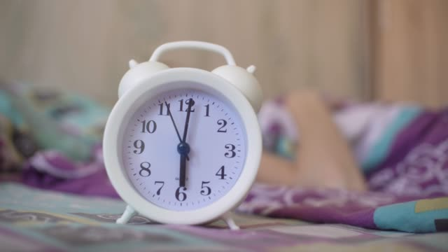 A young woman is lying in bed, the alarm goes off, she turns it off with her hand and the watch falls on its side. Early in the morning! woman's hand turns off alarm clock in morning while lying in bed. life balance stock videos & royalty-free footage