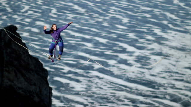 A young woman is on the slackline at high altitude.