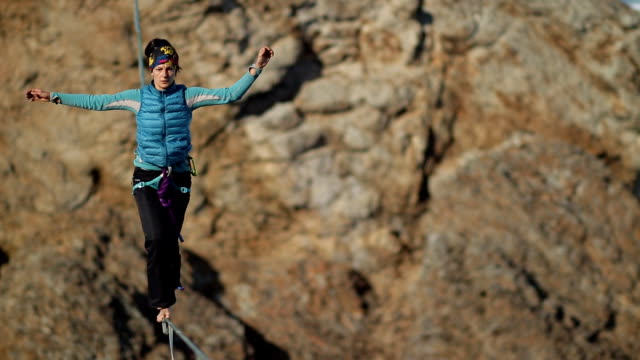 a young woman is on the slackline at high altitude. - coraggio video stock e b–roll