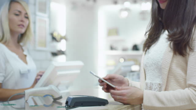 Young woman is paying with her smartphone application at the cash desk in a department store. video