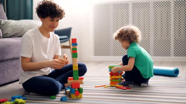 young woman is playing with child with construction blocks, boy is having fun - klocek filmów i materiałów b-roll