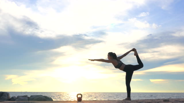 Young woman is practicing yoga on the beach at sunset. Video of Young woman is practicing yoga on the beach at sunset. 4K(UHD) 3840x2160 format. lotus position stock videos & royalty-free footage