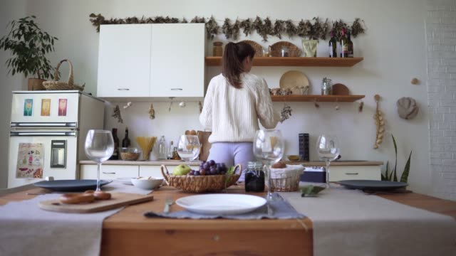 vídeos de stock e filmes b-roll de a young woman is preparing for dinner, standing in the kitchen. loft apartments in scandinavian style, using environmental materials in the interior - hygge
