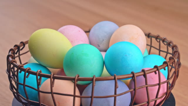 Young woman is preparing for Easter egg hunting, setting decorated colored colorful eggs in a little bamboo basket in home kitchen.