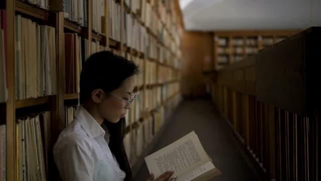 stockvideo's en b-roll-footage met jonge vrouw is het lezen van boek zittend op de vloer in de universiteitsbibliotheek - literatuur