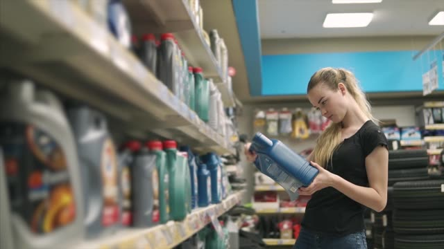 Young woman is reading labels on bottles with machine oil in store