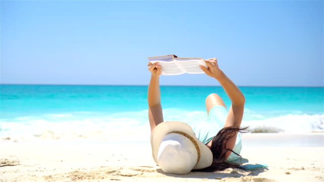 Young woman is reading on tropical white beach