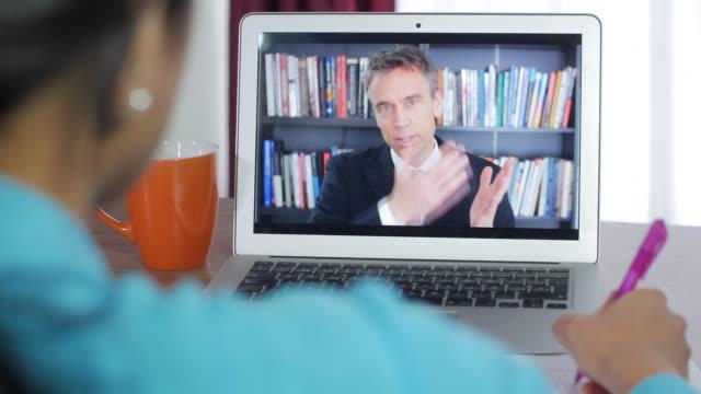 eine junge frau sitzt an einem sauberen schreibtisch und beobachtet einen laptop-bildschirm mit einem live-lehrer, der remote-e-learning-bildung unterrichtet, und erhält eine klasse online. - dozenten stock-videos und b-roll-filmmaterial