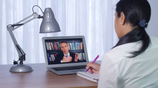 a young woman is sitting at a clean desk watching a laptop screen with a live teacher teaching remote e-learning education, receiving a class online. - odosobniony filmów i materiałów b-roll