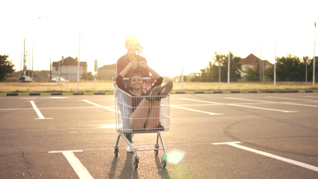 Young woman is sitting in the grocery cart, while her friend is pushing her behind in the parking by the shopping mall, enjoying outdoors with shopping trolley race during sunset. Lens flare Young woman is sitting in the grocery cart, while her friend is pushing her behind in the parking by the shopping mall, enjoying outdoors with shopping trolley race during sunset. Lens flare. woman pushing cart stock videos & royalty-free footage