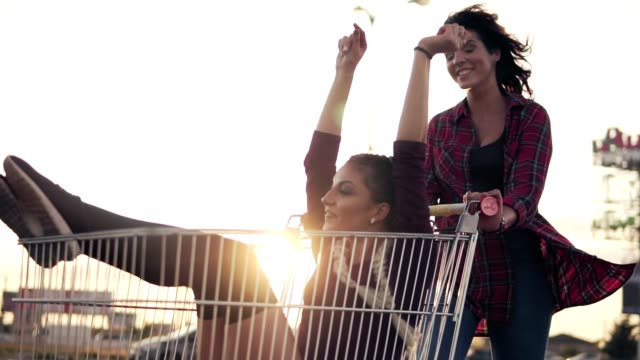 Young woman is sitting in the grocery cart, while her friend is pushing her behind at parking by the shopping mall during sunset. Lens flare. Slowmotion shot Young woman is sitting in the grocery cart, while her friend is pushing her behind at parking by the shopping mall during sunset. Lens flare. Slowmotion shot. woman pushing cart stock videos & royalty-free footage