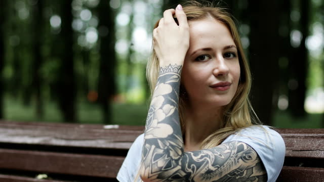 A young woman is sitting on a bench in a park. A young woman is sitting on a bench in a park. A nice girl puts her hair and smiles. tattoo stock videos & royalty-free footage