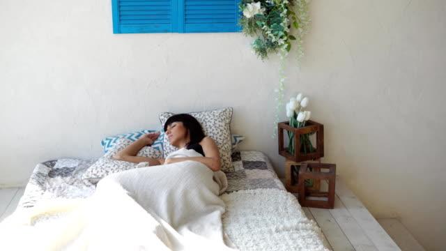 若い女性が寝室で彼女のベッドで枕で寝ています - チャームポイント点の映像素材/bロール