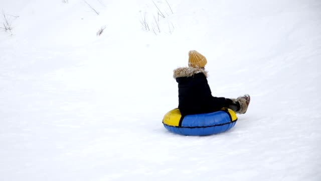 Young woman is sliding from snow hill at tubing in slow motion.