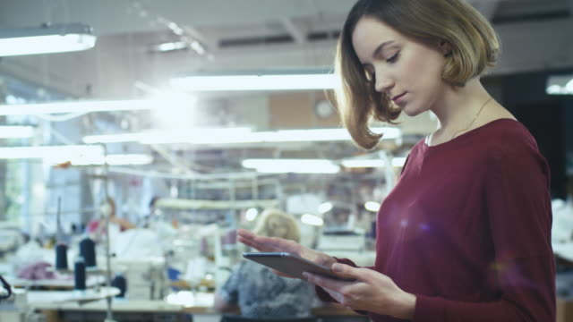 young woman is standing in a clothing factory and using a tablet while employees work in the background. - tailor working video stock e b–roll