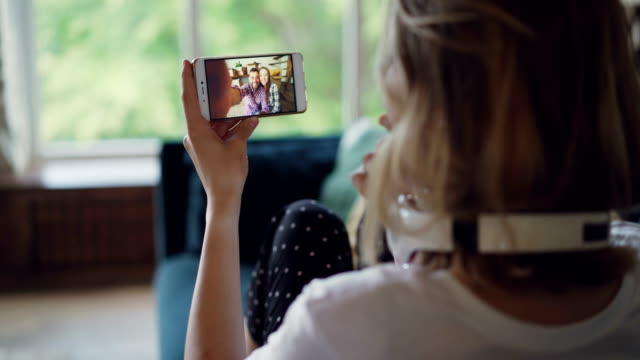 young woman is talking to friends online with smartphone looking at screen and speaking sitting on couch in modern apartment. communication and technology concept. - одна молодая женщина стоковые видео и кадры b-roll