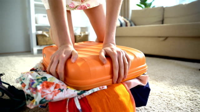 A young woman is trying to close a chock-full orange suitcase. Time lapse video