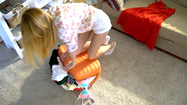 A young woman is trying to close a chock-full orange suitcase. Top view video
