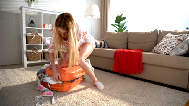 A young woman is trying to close a chock-full orange suitcase video