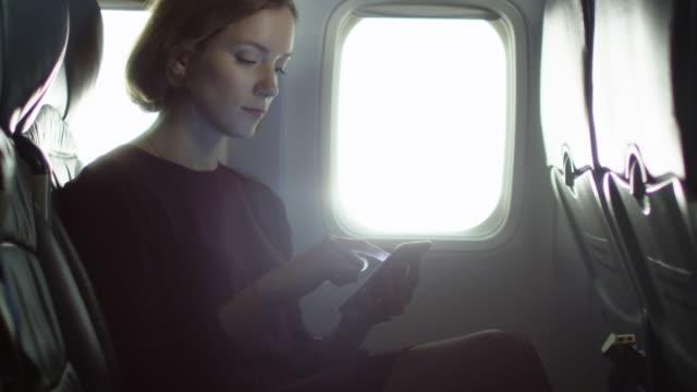 Jeune femme utilise un smartphone à l'intérieur d'un avion à côté d'une fenêtre. - Vidéo