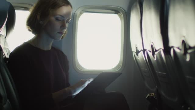 junge frau nutzt eine tablette in einem flugzeug neben einem fenster. - tablet mit displayinhalt stock-videos und b-roll-filmmaterial