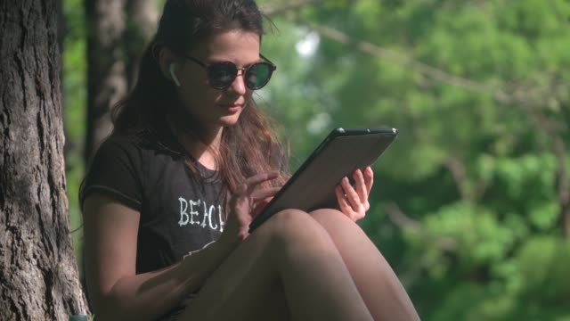young woman is using digital tablet in park - cuffie wireless video stock e b–roll