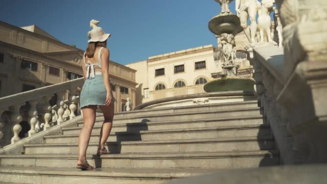 young woman is walking on the stairs in front of praetorian fountain in Palermo