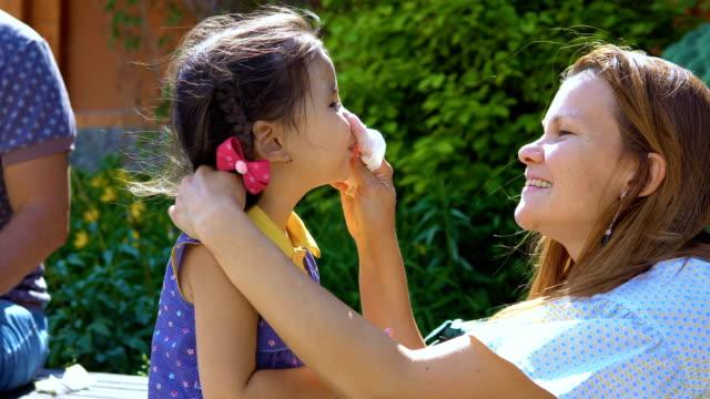 vídeos de stock e filmes b-roll de a young woman is wiping her daughter's face. - boca suja