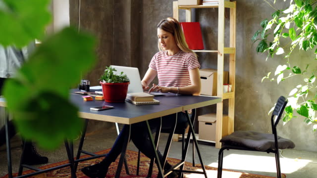 young woman is working with laptop sitting at table in office. her colleague is coming, women start watching screen together and laughing. informal friendly atmosphere. - piccolo ufficio video stock e b–roll