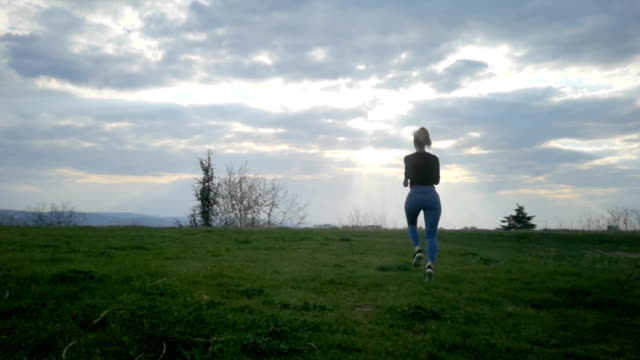 Bидео Young woman jogging at sunset, raises arms into air, youth and happiness, Beautiful clouds and breathtaking sunset. Steadicam slow motion video