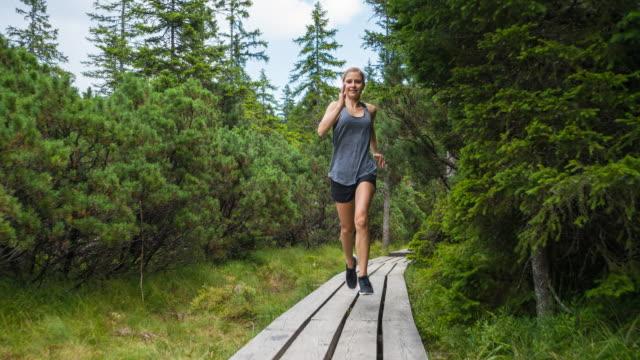 junge frau joggen durch wald unter grünen bäumen an einem schönen tag - gedeihend stock-videos und b-roll-filmmaterial