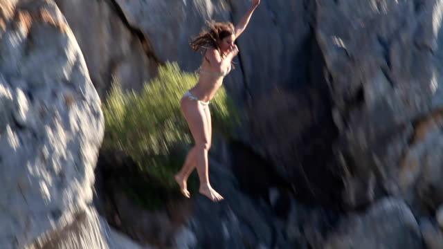Young woman jumping from cliff into sea video