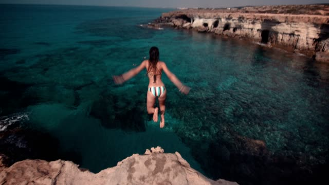 young woman jumping into ocean from rock cliff - vacanze video stock e b–roll